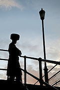 A silhouette of an Orthodox Jewish man wearing a furry hat called a Kolpik, traditional Slavic headdress worn on special occasions. This man is standing at the top of stairs at Watermint Quays while Tach Lich takes place by the river below.