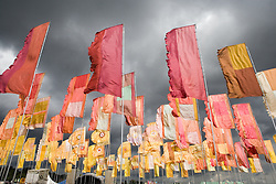 Brooding grey rain clouds over flags flying at the WOMAD (World of Music; Arts and Dance) Festival in reading; 2005,