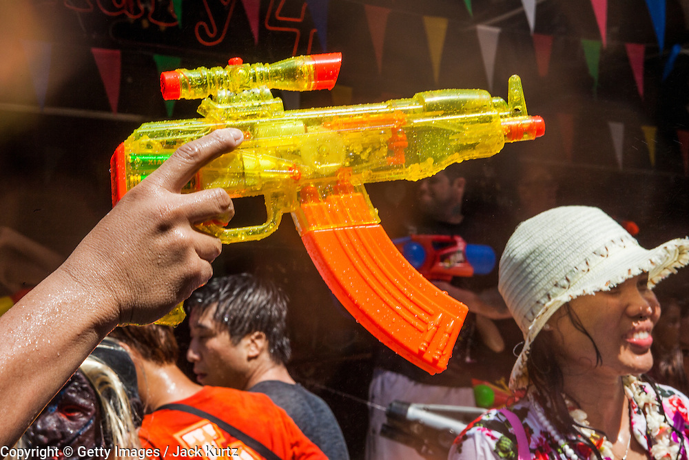 14 APRIL 2013 - BANGKOK, THAILAND:  A tourist holds a water gun above the crowd on Soi Nana on April 14, 2013 in Bangkok, Thailand. The Songkran festival is celebrated in Thailand as the traditional New Year's Day from 13 to 15 April. The throwing of water originated as a way to pay respect to people and is meant as a symbol of washing all of the bad away. PHOTO BY JACK KURTZ