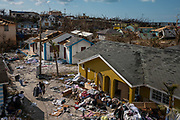 A woman carries a suitcase through a destroyed neighbourhood in the wake of Hurricane Dorian in Marsh Harbour, Great Abaco, Bahamas, September 7, 2019.