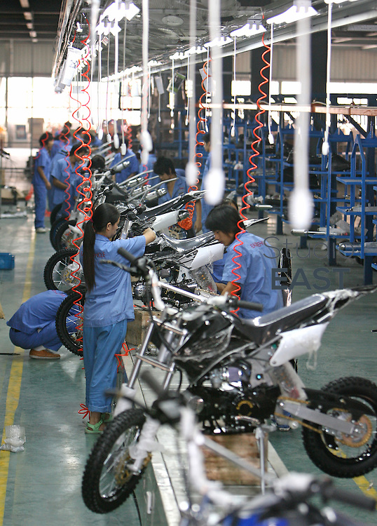 ZHEJIANG PROVINCE, CHINA - September 17: Workers work on an YL306 150 cc dirt bike on the assembly line in Easy vehicle factory on September 17, 2007 in Yong Kang, Zhejiang province, China. (Photo by Lucas Schifres/Getty Images)