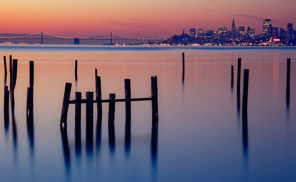 remnants of an old pier stand out as foreground to a sunrise in sausalito california looking toward san francisco with the bay bridge in the background