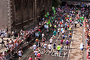 Runners in the London Marathon run along Lower Thames Street. Nearing the end of the race the colourful competitors are cheered by crowds supporting.