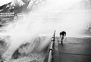 Ducking under the falling spray from a giant wave, a passer-by experience the force of nature from a storm off the coasts of southern England - here at the Port of Dover, Kent. As the water hits the sea defence wall, the seaside town is battered by southerly winds that bring with them huge breakers across the promenade. Adventurous and foolhardy people brave these conditions and stay for as long as possible at the railings then jump out at the last moment before getting doused in salt spray. This man carries on walking and thinks that by bending down, the sea will pass overhead.