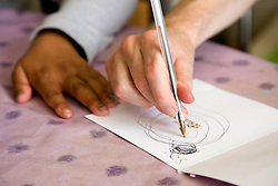 Close up of day service users hand drawing with a pen,