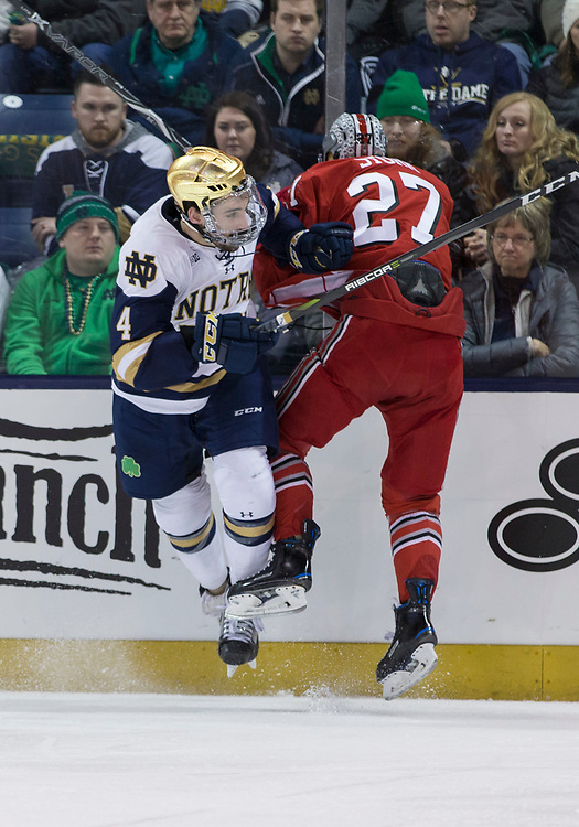 March 17, 2018:  Notre Dame defenseman Dennis Gilbert (4) and Ohio State forward Luke Stork (27) battle along the boards during NCAA Hockey game action between the Notre Dame Fighting Irish and the Ohio State Buckeyes at Compton Family Ice Arena in South Bend, Indiana.  Notre Dame defeated Ohio State 3-2 in overtime.  John Mersits/CSM