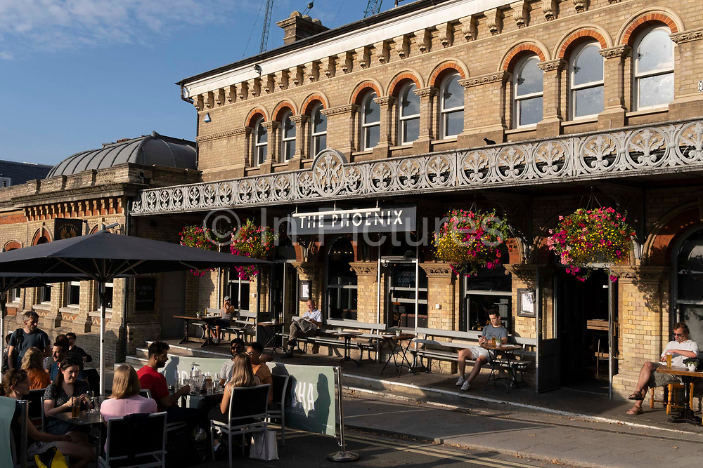 In the week that many more Londoners returned to their office workplaces after the Covid pandemic, drinkers enjoy the late summer sunshine outside the Phoenix pub at Denmark Hill station in Southwark, on 8th September 2021, in London, England. The Phoenix now occupies what was once the main ticket hall of Denmark Hill station, completed in 1866 and designed by Charles Henry Driver in the Italianate style.