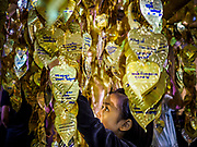 25 OCTOBER 2017 - BANGKOK, THAILAND:  A woman hangs a gold leaf replica of a Bodhi leaf on which she wrote regards for the late king during the funeral for Bhumibol Adulyadej, the Late King of Thailand. He died in October 2016 and was cremated during an ornate five day funeral on 26 October 2017. He reigned for 70 years and was Thailand's longest serving monarch.         PHOTO BY JACK KURTZ