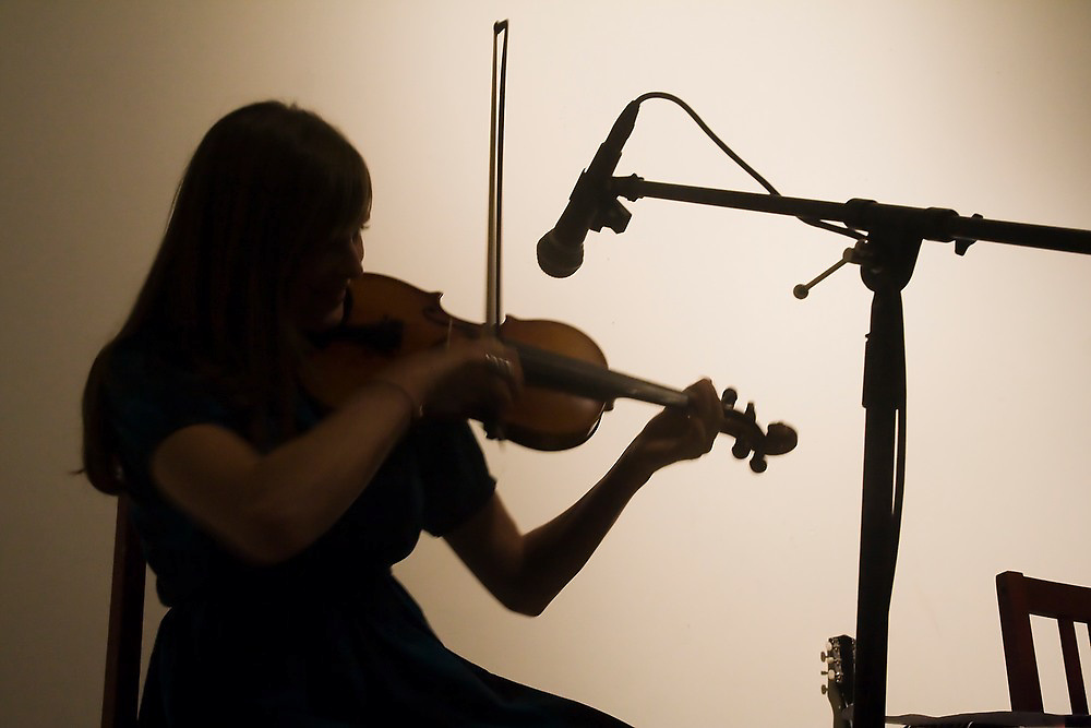 A young female violonist performs at the underground, secretly located Healthy Times Fun Club in Seattle, Washington.