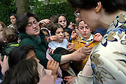 Women and children struggle to get vouchers for free kosher ice cream, the only kosher ice cream van in the UK visiting a community event in Allen Gardens, Stamford Hill to celebrate Lag B'Omer. Lag B'Omer is the holiday celebrating the thirty-third day of the (counting of the) Omer. Jews celebrate it as the day when the plague that killed 24,000 people ended in the holy land (according to the Babylonian Talmud). Other sources say the plague was actually the Roman occupation and the 24,000 people died in the second Jewish - Roman war  (Bar Kokhba revolt of the first century).  Bonfires (used as signals in wartime) are symbolically lit to commemorate the holiday of Lag'B'Omer.