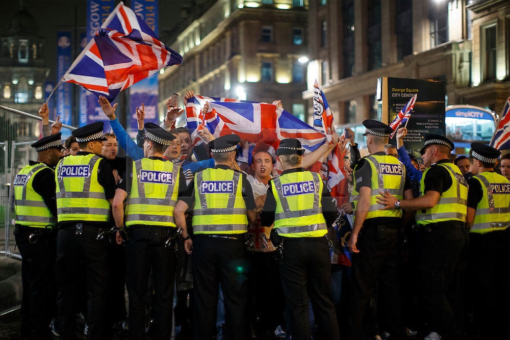 © Licensed to London News Pictures. 19/09/2014. Glasgow, UK. Pro-Unionists posing against Scottish independence supporters at George Square in Glasgow as Scotland decides to stay in the union and First Minister Alex Salmond resigns over the results of the Scottish independence referendum on Friday, 19 September 2014. Photo credit : Tolga Akmen/LNP