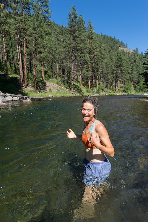 Woman standing in the Minam River, Wallowa Mountains, Oregon.