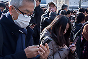 Workers check cellphones for news as they  wait outside their office buildings near Ochanomizu Station  after a magnitude .9 earthquake hit the Tohoku region of north east Japan causing tremors in Tokyo that stopped the train and cellphone networks. Many people were stranded in the centre of Tokyo over night. Tokyo, Japan Friday March 11th 2011