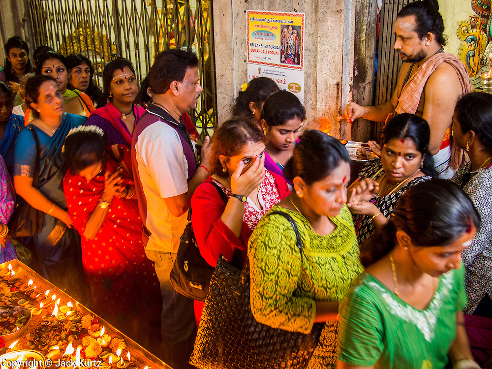 07 JANUARY 2014 - SINGAPORE:   People receive blessings from a Hindu priest during afternoon pooja at Sri Veeramakaliamman Temple, a Hindu temple located in Little India in the southern part of Singapore. The Sri Veeramakaliamman Temple is dedicated to the Hindu goddess Kali, fierce embodiment of Shakti and the god Shiva's wife, Parvati. Kali has always been popular in Bengal, the birthplace of the labourers who built this temple in 1881. Images of Kali within the temple show her wearing a garland of skulls and ripping out the insides of her victims, and Kali sharing more peaceful family moments with her sons Ganesha and Murugan. The building is constructed in the style of South Indian Tamil temples common in Tamil Nadu as opposed to the style of Northeastern Indian Kali temples in Bengal. PHOTO BY JACK KURTZ