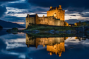Eilean Donan Castle looks spectacular when spotlit at twilight, in Kintail National Scenic Area, Scotland, United Kingdom, Europe. This picturesque island stronghold was first built in the 1200s in the western Highlands where three sea lochs meet (Loch Duich, Loch Long, and Loch Alsh) at the village of Dornie. Since restoration in the early 1900s, a footbridge connects the island to the mainland. The island is named after Donnán of Eigg, a Celtic saint martyred in 617. The castle became a stronghold of the Clan Mackenzie and their allies Clan Macrae. In the early 1700s, the Mackenzies' involvement in the Jacobite rebellions led in 1719 to the castle's destruction by government ships. Lieutenant-Colonel John Macrae-Gilstrap's 1920-32 reconstruction of the ruins made the present buildings.