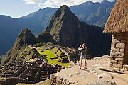 Young girl at a guard house photographing the Citadel at Machu Picchu