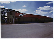 "Elongated building with ""Taylors"" painted on roof alongside highway.<br /> Dolores, CO"