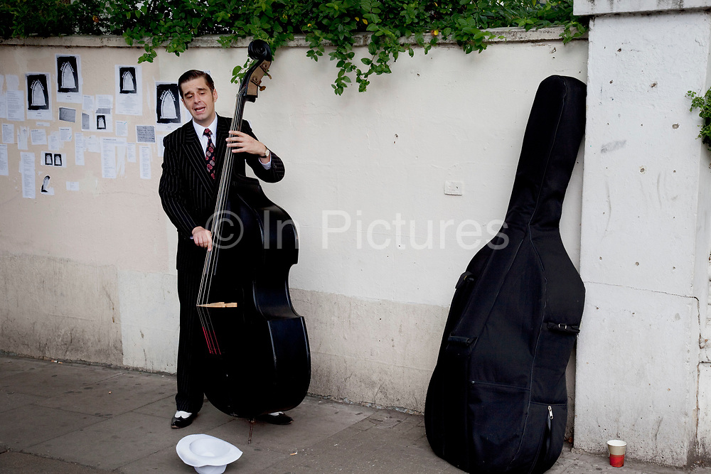 Busker witha  double bass on Portobello Road market, Notting Hill, West London. This famous Sunday market is when the antique stalls come out as well as the food stalls.
