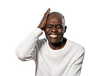Close-up of an afro American man with a severe headache in studio on white isolated background
