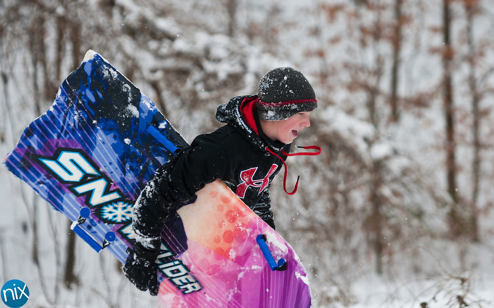 Will Horsley, 13, of Concord runs up a hill after sledding down it at Les Myers Park in Concord Monday morning. A winter storm continued cover the region throughout the day, closing schools and many businesses. (Photo by James Nix)