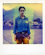 Portrait of a vietnamese man standing in a parking lot. Northern Vietnam, Asia. The polaroid is really outdated and present a blue trace on its surface