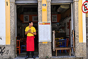 A waiter looks out from an empty cafe before the dinner crowd arrives in the Santa Teresa neighborhood in Rio de Janeiro, Brazil.