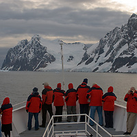 Tourists aboard the National Geographic Endeavor admire mountains above the Lemaire Channel, Antarctica.