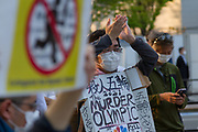 """A man applauds speeches wearing a sign saying """"The Murder Olympics"""" as people take part in a demonstration against the delayed 2020 Tokyo Olympics Games in Gaiemmae, Tokyo, Japan. Sunday May 9th 2021. About 100 people took part in a demo outside the Japanese Olympic Committee museum and marched around the new Olympic Stadium to protest holding the event while the  the COVID-19 pandemic is still seriously affecting Japan."""