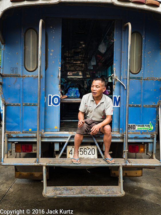 26 OCTOBER 2016 - NUPO TEMPORARY SHELTER, MAE CHAN, TAK, THAILAND:  A Burmese man sits on the back step of the bus that took him back to Myanmar during his repatriation. Sixtyfive Burmese refugees living in the Nupo Temporary Shelter refugee camp in Tak Province of Thailand were voluntarily repatriated to Myanmar. About 11,000 people live in the camp. The repatriation was the first large scale repatriation of Myanmar refugees living in Thailand. Government officials on both sides of the Thai / Myanmar border said the repatriation was made possible by recent democratic reforms in Myanmar. There are approximately 150,000 Burmese refugees living in camps along the Thai / Myanmar border. The Thai government has expressed interest several times in the last two years in starting the process of repatriating the refugees.    PHOTO BY JACK KURTZ