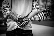 03252017 - Indianapolis, Indiana, USA: A Trump supporter holds an American flag as members of the Vinlanders Social Club, a skinhead group, stand on a sidewalk outside the Indiana Statehouse during a Make America Great Again rally.