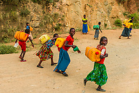 Konso tribe girls walking back from a stream with water jugs. near Omo Valley, Ethiopia.