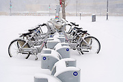 29 DECEMBER 2020 - DES MOINES, IOWA: Bicycles at a bike rental station are covered in show during the heaviest snowfall so far of the 2020-21 winter. Des Moines was expected to get about 8 inches of snow before Wednesday morning. Statewide, across Iowa, more than 900 snowplows have been called out to clear the roads.       PHOTO BY JACK KURTZ