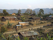 View of Ban Sanamjab Ko Loma ethnic minority village in Phongsaly Province, Lao PDR. Since the village relocated to be beside a small road the grass roofs of the houses have been replaced by corregated metal and the village now has easier access to education, medical facilities and markets.