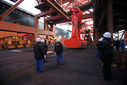 Dock workers inspects a mechanical scoop at an iron-ore transfer and storage center operated by the Shanghai International Port Group in Shanghai, China on 26 January 2010.  China's economic boom and hunger for natural resources has been a blessing for countries such as Australia and Brazil, who controls most the world's high quality iron ore deposits.