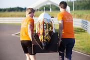 De fiets wordt naar een werkplek gedragen na een klapband. Het Human Power Team Delft en Amsterdam (HPT), dat bestaat uit studenten van de TU Delft en de VU Amsterdam, is in Senftenberg voor een poging het laagland sprintrecord te verbreken op de Dekrabaan. In september wil het Human Power Team Delft en Amsterdam, dat bestaat uit studenten van de TU Delft en de VU Amsterdam, tijdens de World Human Powered Speed Challenge in Nevada een poging doen het wereldrecord snelfietsen voor vrouwen te verbreken met de VeloX 7, een gestroomlijnde ligfiets. Het record is met 121,44 km/h sinds 2009 in handen van de Francaise Barbara Buatois. De Canadees Todd Reichert is de snelste man met 144,17 km/h sinds 2016.<br /> <br /> The Human Power Team is in Senftenberg, Germany to race at the Dekra track as a preparation for the races in America. With the VeloX 7, a special recumbent bike, the Human Power Team Delft and Amsterdam, consisting of students of the TU Delft and the VU Amsterdam, also wants to set a new woman's world record cycling in September at the World Human Powered Speed Challenge in Nevada. The current speed record is 121,44 km/h, set in 2009 by Barbara Buatois. The fastest man is Todd Reichert with 144,17 km/h.