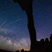 Landscape Arch silhouetted by the night sky and star trails of the moving earth and milky way near Moab, Utah.