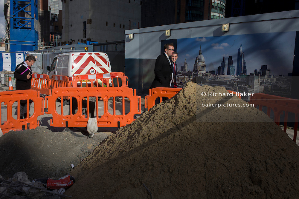 City workers walk past roadworks and pavement construction disruption in the City of London.