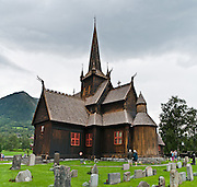 """Built in 1170, Lom Stave Church (stavkirke or stavkyrkje) was rebuilt into a cruciform, triple-nave church in 1663 and restored in 1933 and 1973. Visit this wooden Norman-style church in the town of Lom, in Gudbrandsdal traditional district, Oppland county, Norway. """"Staves"""" are upright logs that support the central room framework. Panorama stitched from 2 overlapping photos."""