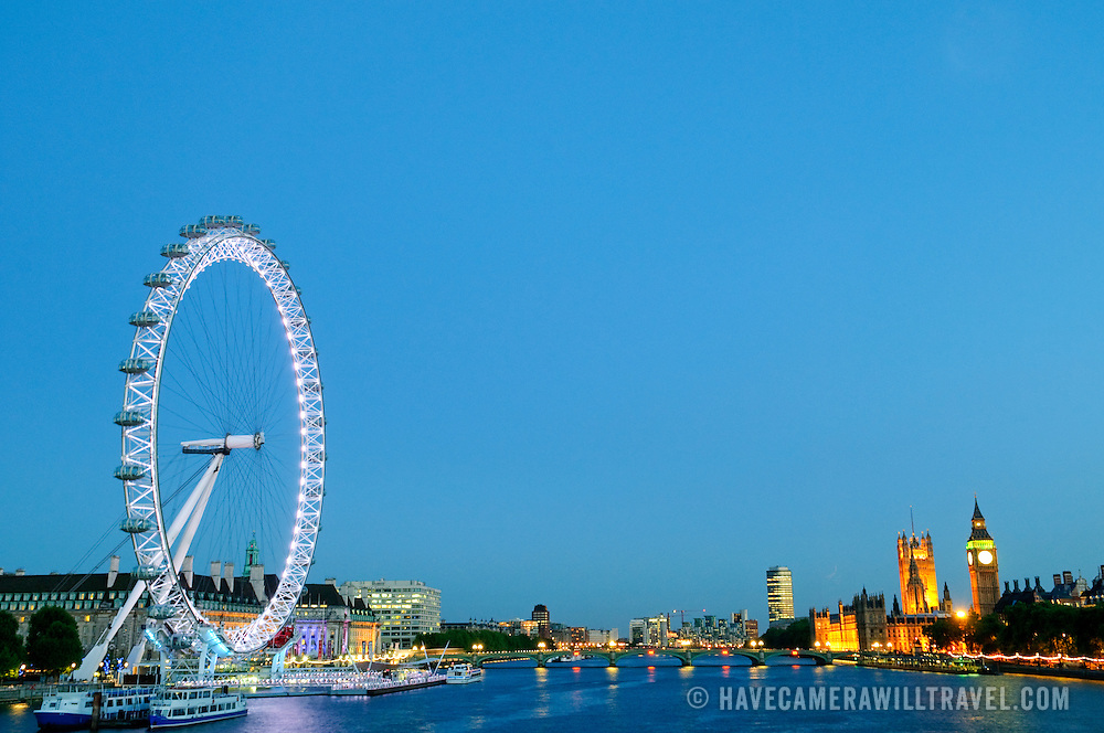 London's Millennium Wheel and Houses of Parliament on the River Thames at dusk.