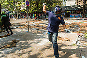 26 DECEMBER 2013 - BANGKOK, THAILAND: An anti-government protestor throws rocks towards Thai police positions. Thousands of anti-government protestors flooded into the area around the Thai Japan Stadium to try to prevent the drawing of ballot list numbers by the Election Commission, which determines the order in which candidates appear on the ballot of the Feb. 2 election. They were unable to break into the stadium and ballot list draw went as scheduled. The protestors then started throwing rocks and small explosives at police who responded with tear gas and rubber bullets. At least 20 people were hospitalized in the melee and one policeman was reportedly shot by anti-government protestors.      PHOTO BY JACK KURTZ