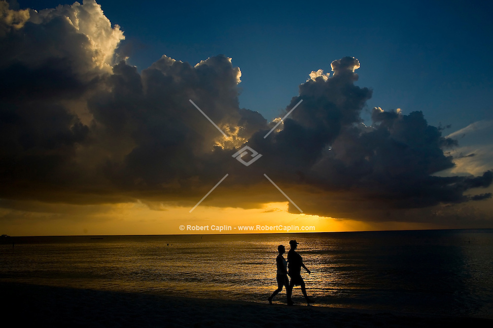 Jeannelle Fuentes Mora, left, and Andrew Gresham (holding 6-week-old baby Isabelle) enjoy a walk along 7-mile beach during the sunset in the Cayman Islands, British West Indies. Both reside in the Cayman Islands. Oct. 10, 2006.