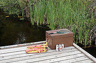This dock on Blackburn Lake (between Ganges and Fulford Harbour) is clothing optional, but also appears to be a spot for fishing and drinking.  Photographed at Blackburn Lake on Salt Spring Island, British Columbia, Canada.