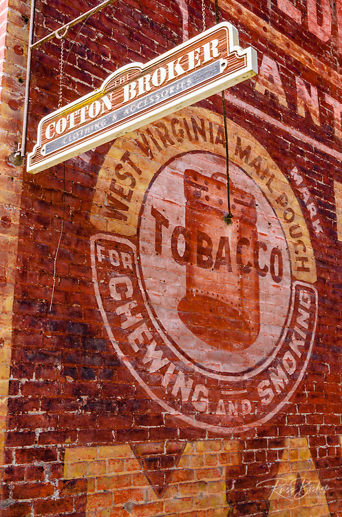 Historic advertisement on brick building and modern shop sign, Jacksonville, Oregon USA