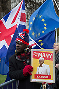 Joseph Afrane with a pro-labour sign outside the Houses of Parliament the day after Theresa Mays crushing defeat over her Brexit deal on the 16th January 2019 in London in the United Kingdom. Prime Minister Theresa May is expected to win a confidence vote on the 16th, despite a crushing defeat over her Brexit deal.