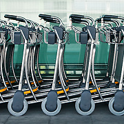 A row of empty luggage carts at an airport.<br /> <br /> LICENSING: This image can be licensed through SpacesImages. Click on the link below:<br /> <br /> http://tinyurl.com/bpzlvqd