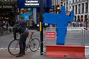 The back of a road crossing figure and a cyclist at the junction of Oxford Street and Tottenham Court Road.