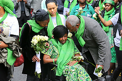 © Licensed to London News Pictures. 14/06/2019. London, UK.  A woman wearing a symbolic green scarf reacts as she takes part in a ceremony to commemorate the second anniversary of the Grenfell Tower fire. On 14 June 2017, just before 1:00 am a fire broke out in the kitchen of the fourth floor flat at the 24-storey residential tower block in North Kensington, West London, which took the lives of 72 people. More than 70 others were injured and 223 people escaped. Photo credit: Dinendra Haria/LNP