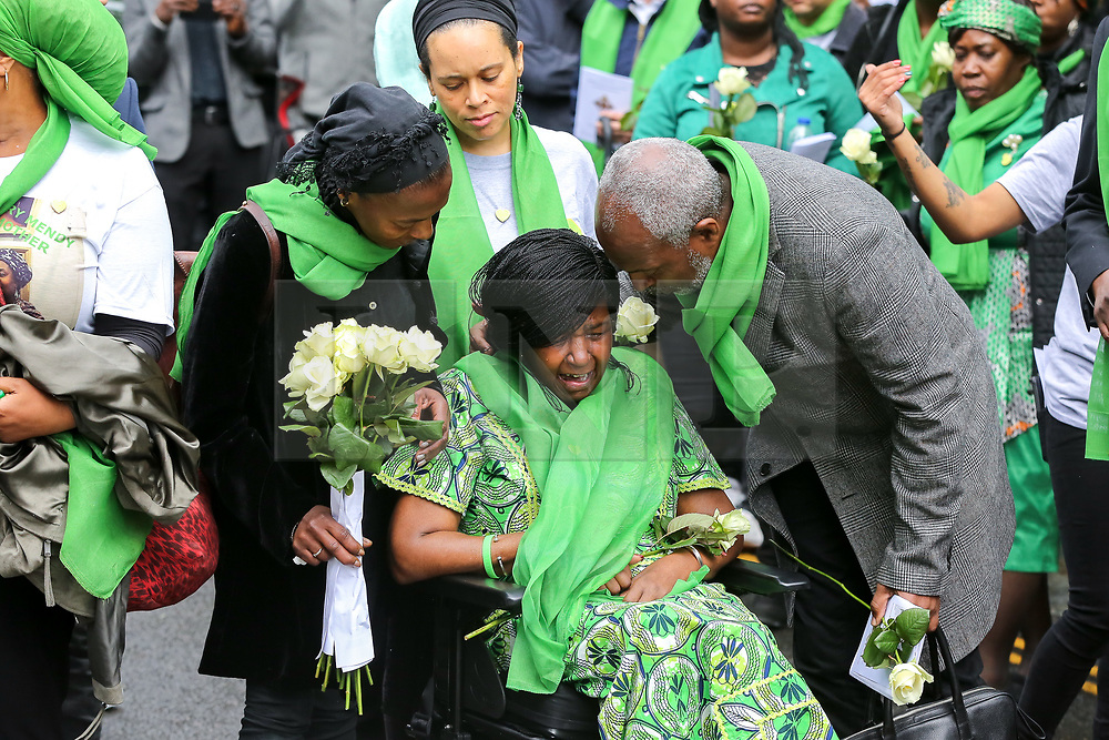 © Licensed to London News Pictures. 14/06/2019. London, UK.  A woman wearing a symbolic green scarf reacts as she takes part in a ceremony to commemorate the second anniversary of the Grenfell Tower fire. On 14 June 2017, just before 1:00am a fire broke out in the kitchen of the fourth floor flat at the 24-storey residential tower block in North Kensington, West London, which took the lives of 72 people. More than 70 others were injured and 223 people escaped. Photo credit: Dinendra Haria/LNP