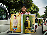 25 OCTOBER 2015 - SHWEPYITHAR, MYANMAR: A vendor walks through traffic in Yangon, Myanmar, selling calendars with photos of Aung San Suu Kyi. Political parties are in fill campaign mode in Myanmar (Burma). National elections are scheduled for Sunday Nov. 8. The two principal parties are the National League for Democracy (NLD), the party of democracy icon and Nobel Peace Prize winner Aung San Suu Kyi, and the ruling Union Solidarity and Development Party (USDP), led by incumbent President Thein Sein. There are more than 30 parties campaigning for national and local offices.     PHOTO BY JACK KURTZ
