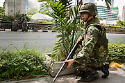 May 19 - BANGKOK, THAILAND: A Thai solder takes cover from suspected snipers along Ratchadamri Road opposite Lumpini Park during the Thai government crack down against Red Shirt and anti government protesters. The Royal Thai Army attacked anti-government protesters May 19 with troops and armored personnel carriers. Photo by Jack Kurtz
